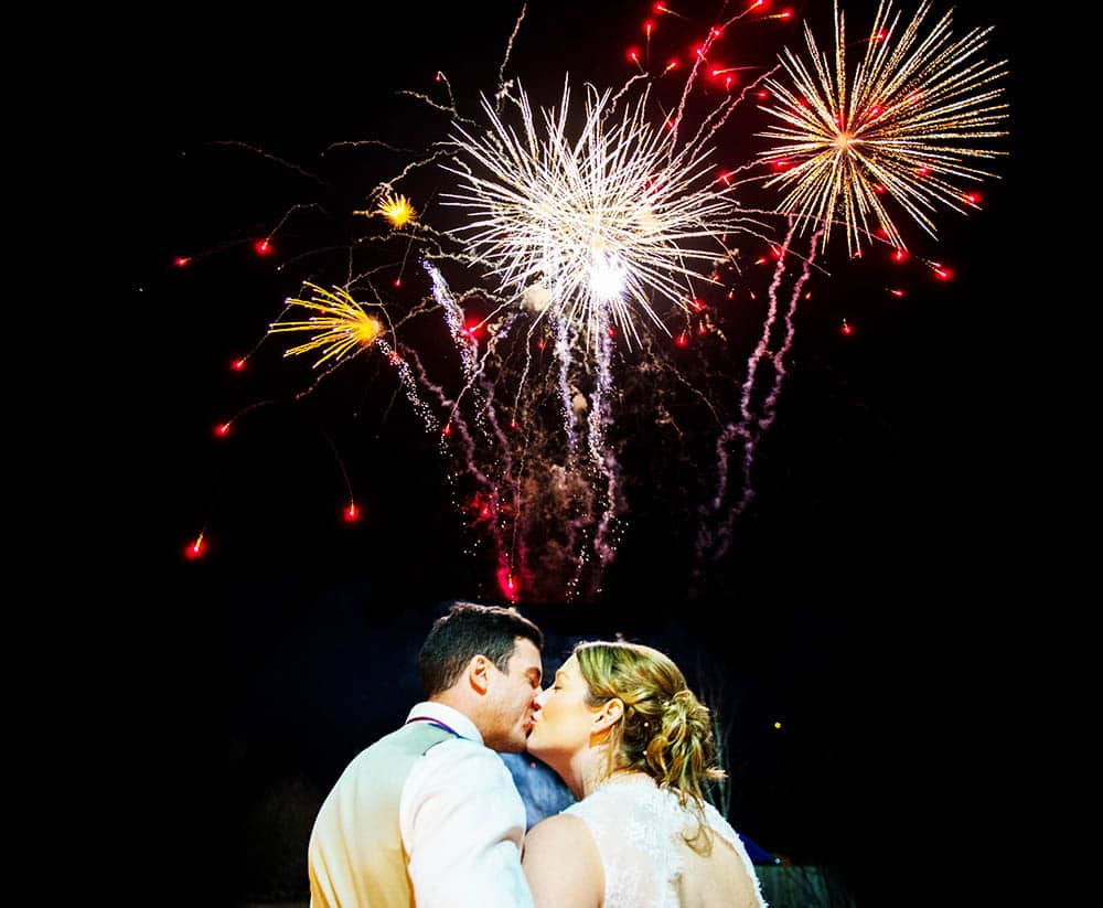 A wedding photograph of a bride and groom kissing in front of Fireworks in Nottingamshire