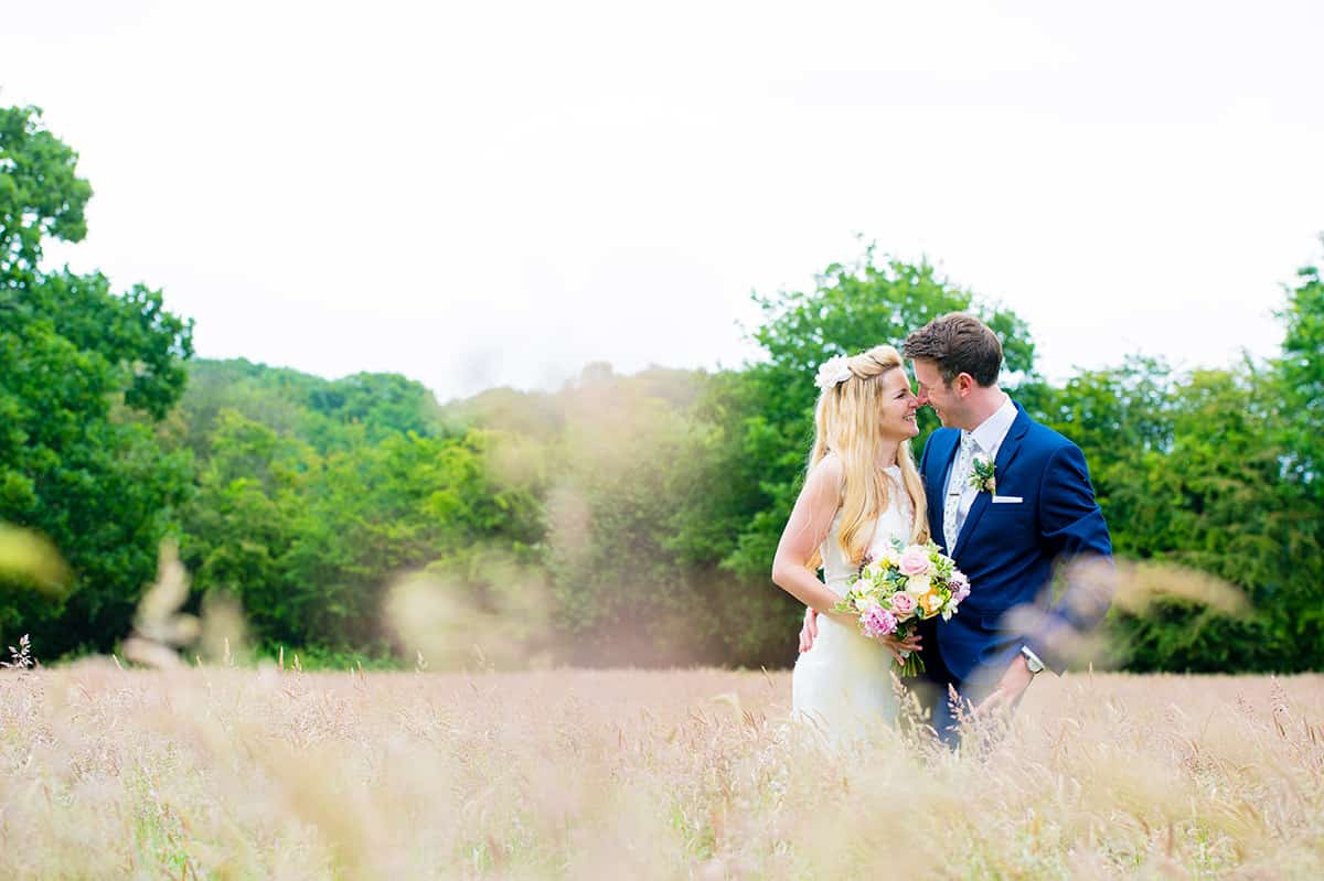 Bride and Groom in a summer field kissing on their wedding day