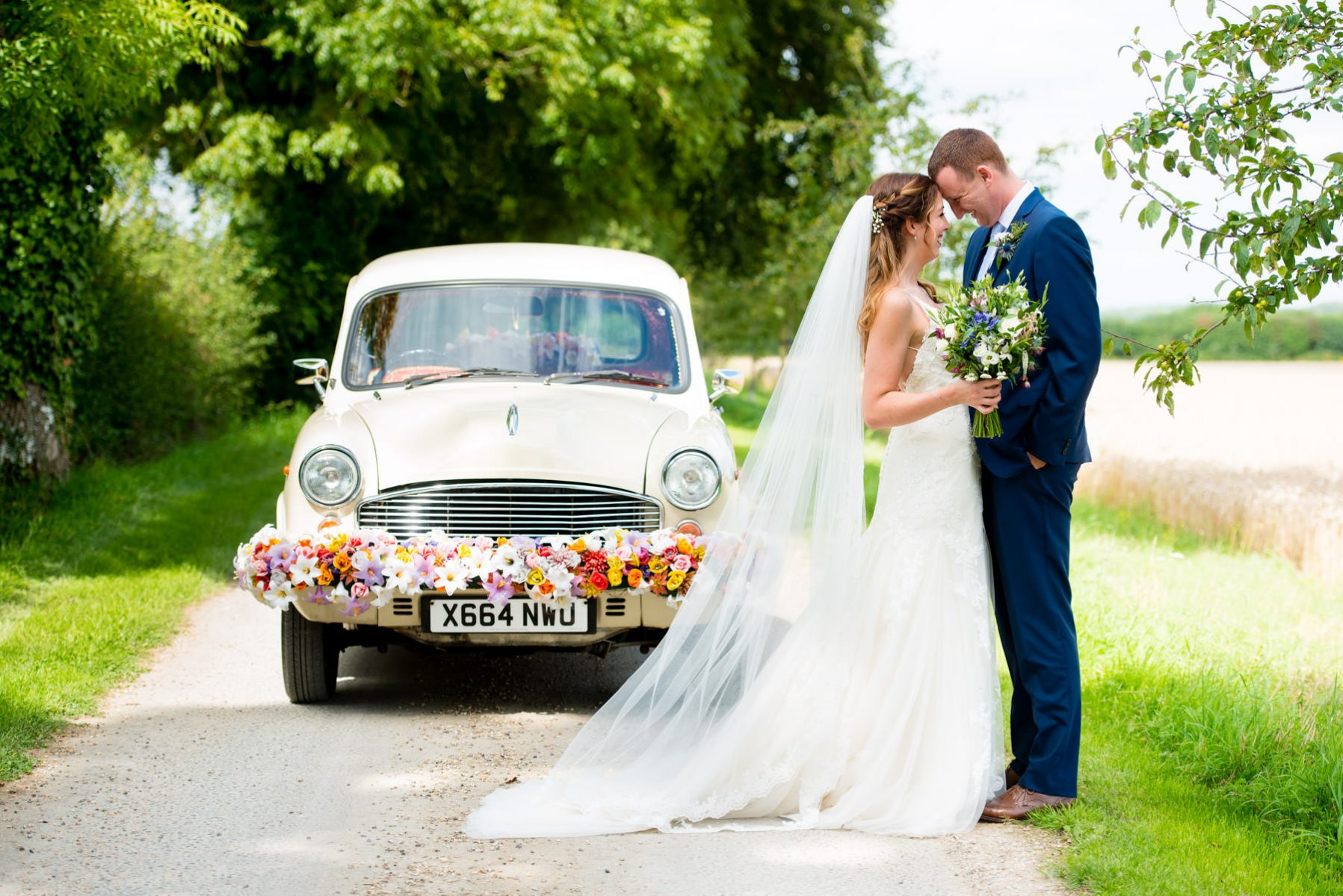 Bride and groom kissing next to wedding car